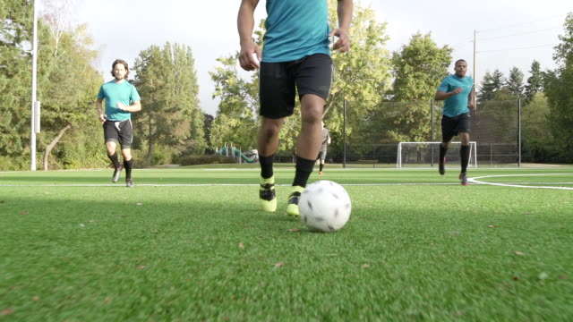 stockvideo's en b-roll-footage met male soccer players playing soccer with man dribbling ball ahead. - schoppen lichaamsbeweging