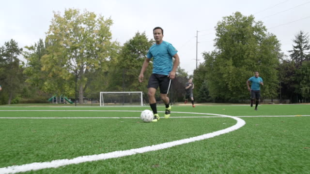 male soccer players playing soccer with man dribbling ball ahead. - football team stock videos & royalty-free footage