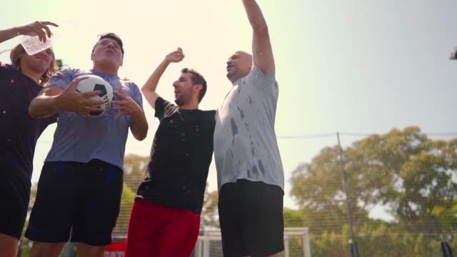 männliche fußballer stehen auf dem fußballplatz und feiern den sieg - sportmannschaft stock-videos und b-roll-filmmaterial