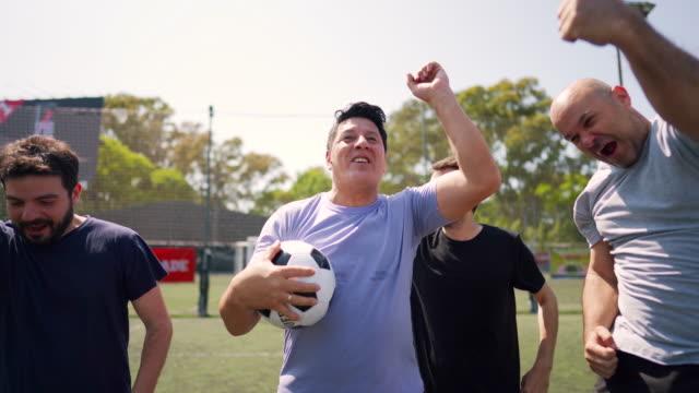 vídeos de stock, filmes e b-roll de jogadores de futebol masculinos em pé em campo de futebol e celebrando a vitória - termo esportivo