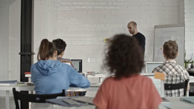 Male software developer teaching coding to school children