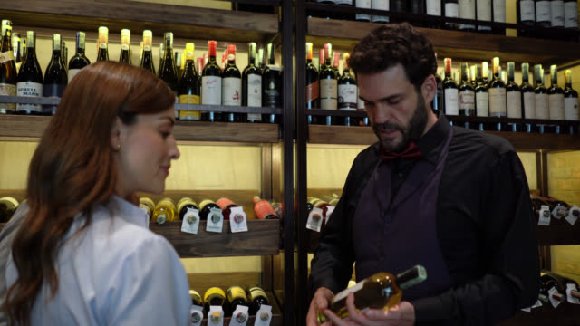 male sommelier grabbing a bottle from rack suggesting a white wine to customer couple - wine bar stock videos & royalty-free footage