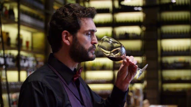 vídeos de stock e filmes b-roll de male sommelier tasting wine while working at a cellar - provar