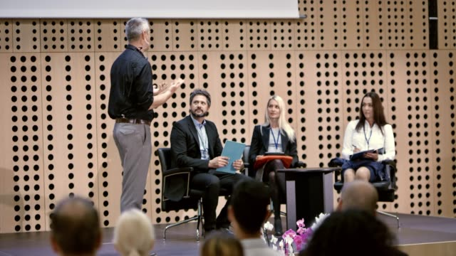 Male speaker talking to his guests seated on the stage at a seminar