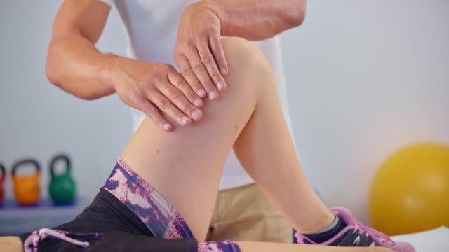 stockvideo's en b-roll-footage met slo mo mannelijke sportmassage therapeut masseren knie van een cliënt - massagetafel