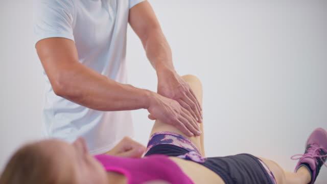 stockvideo's en b-roll-footage met slo mo mannelijke sportmassage therapeut masseren van een vrouwelijke cliënt been - massagetafel