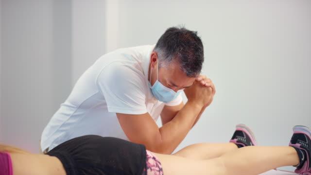 stockvideo's en b-roll-footage met slo mo mannelijke sportmassagetherapeut die een masker draagt terwijl het masseren van het been van zijn vrouwelijke cliënt - massagetafel