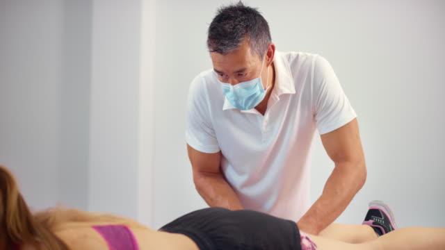 stockvideo's en b-roll-footage met slo mo mannelijke sportmassagetherapeut die een masker draagt terwijl het masseren van zijn vrouwelijke cliënt - massagetafel