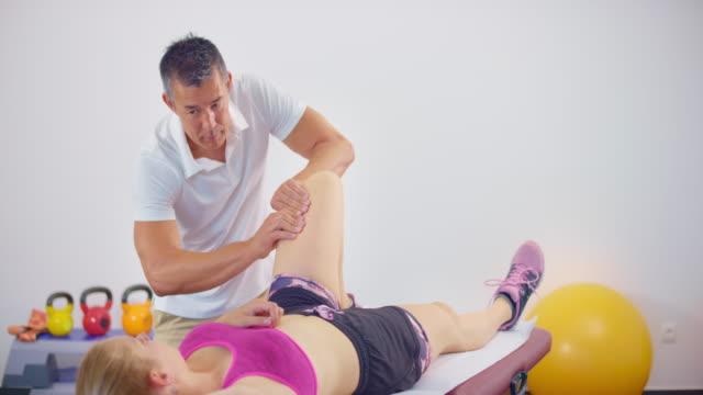 stockvideo's en b-roll-footage met slo mo mannelijke sportmassagetherapeut die met een vrouwelijke cliënt werkt en terwijl het masseren van haar knie spreekt - massagetafel
