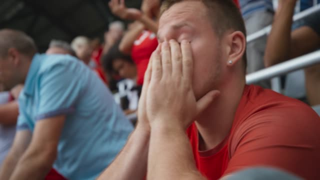 stockvideo's en b-roll-footage met male sports fan sitting on the tribune and covering his face in disappointment at the score - teleurstelling