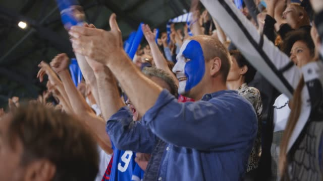 male sports fan with a painted face celebrating on the stadium tribune - face paint stock videos & royalty-free footage