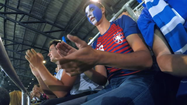 ld male sports fan with a painted face doing the mexican wave on the stadium tribune - face paint stock videos & royalty-free footage