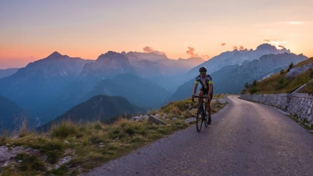 日の出の山道でサイクリングをする男性 sportsperson - アウトドア点の映像素材/bロール