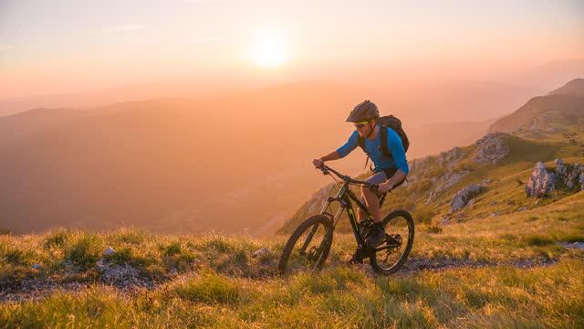 vídeos y material grabado en eventos de stock de deportista masculino todoterreno ciclismo cuesta arriba en un hermoso día soleado, montañas en capas en el fondo - mountain bike