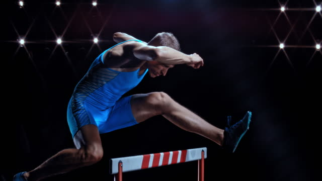 slo mo ds male sprinter  in blue outfit jumping over a hurdle at night - track and field event stock videos and b-roll footage