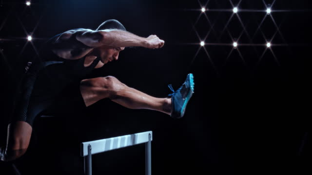 slo mo ds male sprinter jumping over a hurdle at night - track and field event stock videos and b-roll footage