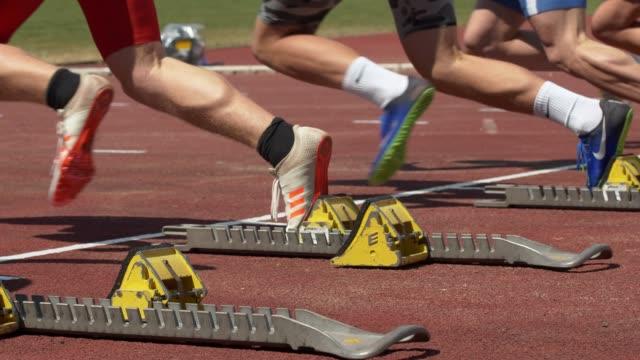 vidéos et rushes de male sprinters starting from the starting block - départ