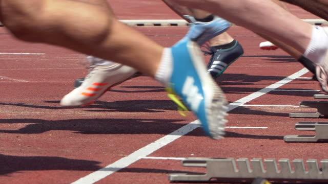 male sprinters starting from the starting block - blocco di partenza per l'atletica video stock e b–roll