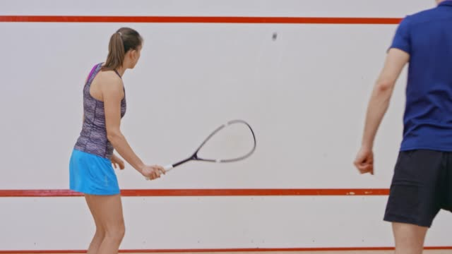 male squash coach teaching a young woman how to improve her forehand - squash sport stock videos & royalty-free footage