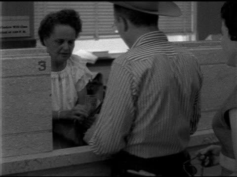 male standing at open teller w/ female bank employee behind counter, teller counting out bills to customer, woman stepping up to counter w/ purse... - 1952 bildbanksvideor och videomaterial från bakom kulisserna