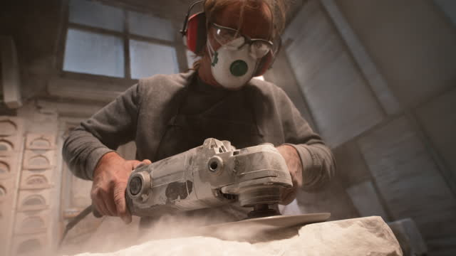 slo mo ld male stonemason using a power tool to smoothen the surface of white stone - sculpture stock videos & royalty-free footage