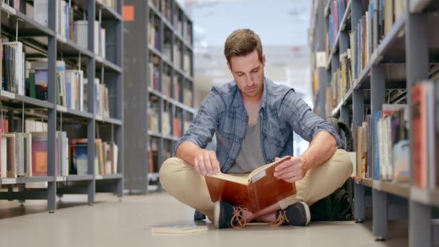 ds männliche schüler lesen ein buch in der bibliothek sitzt gang - konzentration stock-videos und b-roll-filmmaterial