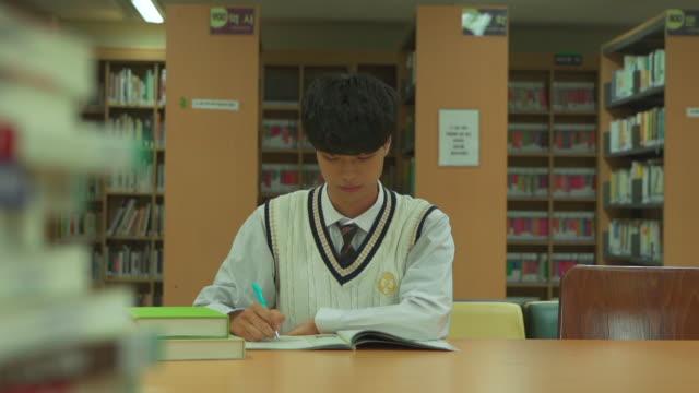 vídeos y material grabado en eventos de stock de a male student sitting and studying in the library - articulación humana