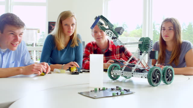 vidéos et rushes de ms male student sitting with smiling classmates in high school classroom operating robot on table with remote control. - montrer la voie