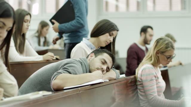 vídeos y material grabado en eventos de stock de estudiante masculino dormir en montaje tipo aula - dormir