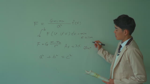 a male student solving a math problem on the board - 黒板点の映像素材/bロール