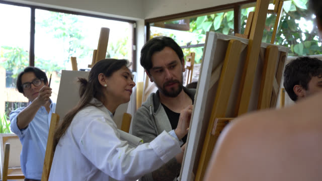 male student talking to his teacher about his sketch while she points at the canvas giving feedback - professional painter stock videos and b-roll footage