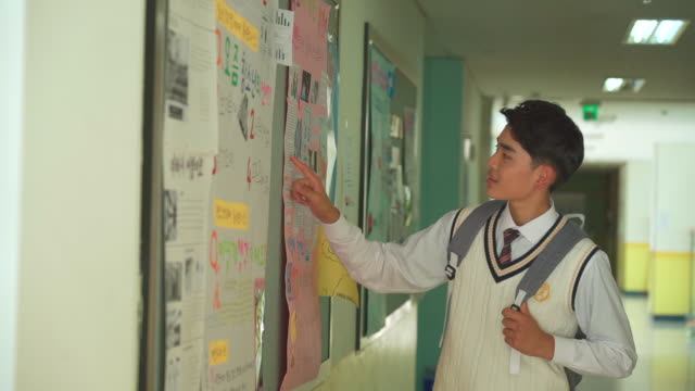 a male student watching a board in the hallway of classroom - school uniform stock videos & royalty-free footage