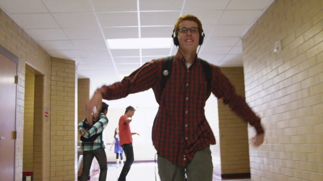 vídeos de stock, filmes e b-roll de ms slo mo male student (16-17) wearing headphone dancing in school corridor / spanish fork city, utah, usa - colégio educação
