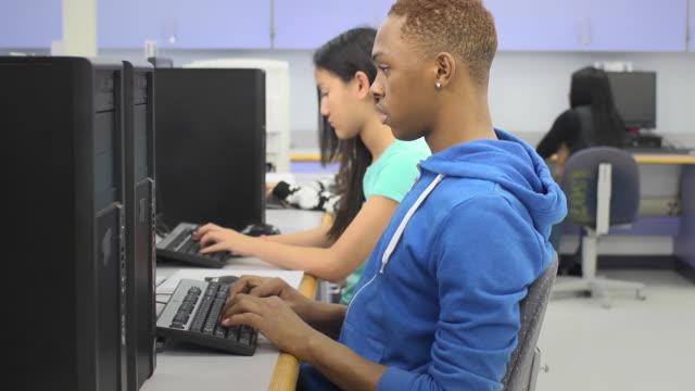 vídeos y material grabado en eventos de stock de estudiante masculino trabaja en el ordenador en montaje tipo aula - laboratorio de ordenadores