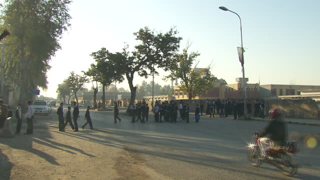 male students standing in groups on shaded median & roadside outside islamabad model college for boys, light traffic passing fg. south asia, capital,... - median nerve stock videos & royalty-free footage