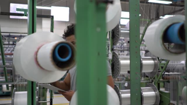 männlicher vorgesetzter überprüft die produktion von gummibändern, während sie eine tablette halten - qualitätsprüfer stock-videos und b-roll-filmmaterial