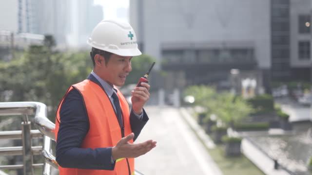 男性上司たちは、工場でトランシーバーを使用して、建設現場でトランシーバーを使用して - ヘルメット点の映像素材/bロール