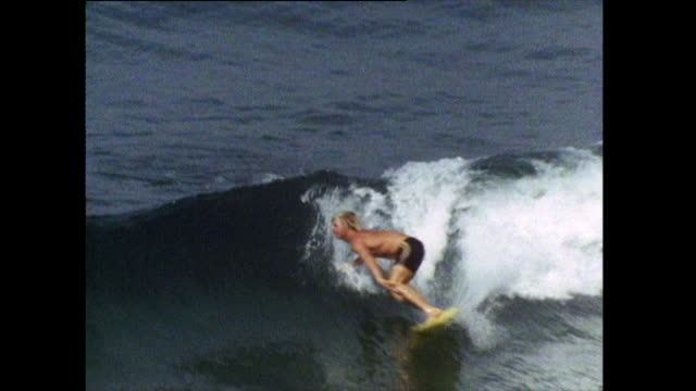 male surfer rides a wave in hermosa beach; 1972 - semi dress stock videos & royalty-free footage