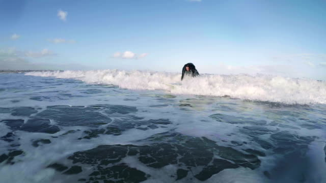male surfer rides the waves - diving suit stock videos and b-roll footage