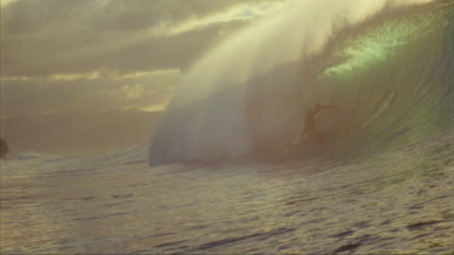 vídeos de stock, filmes e b-roll de slo mo, ws, male surfer riding banzai pipeline at sunset, oahu's north shore, hawaii, usa - diving suit