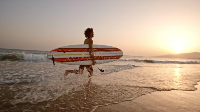 slo mo manliga surfare som kör i det grunda vattnet på stranden vid solnedgången med en surfbräda i famnen - surfbräda bildbanksvideor och videomaterial från bakom kulisserna