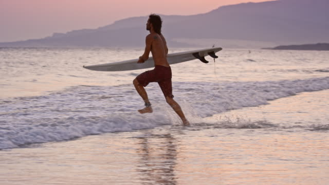 SLO MO Male surfer running into the water with his surf board at sunset