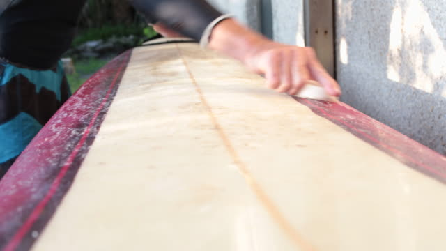 cu male surfer waxing board - old diving suit stock videos and b-roll footage