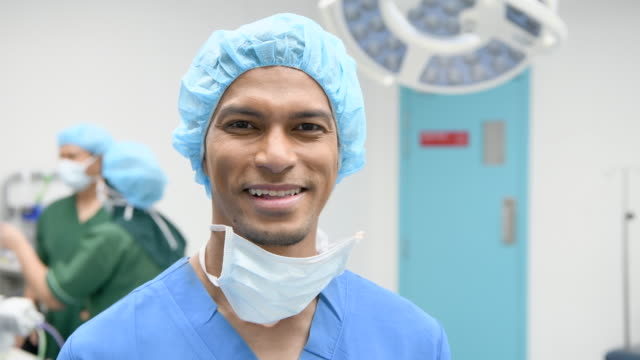 male surgeon in scrubs smiling at camera - surgeon stock videos & royalty-free footage