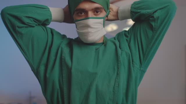 vídeos y material grabado en eventos de stock de cirujano masculino pone en una cara una máscara médica en la sala de operaciones - cirujano