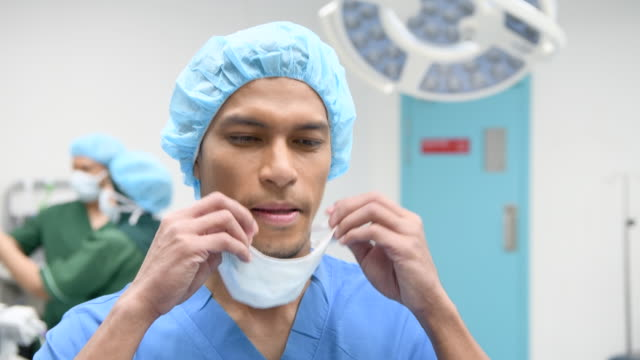 male surgeon putting on surgical mask in operating theatre - scrubs stock videos & royalty-free footage
