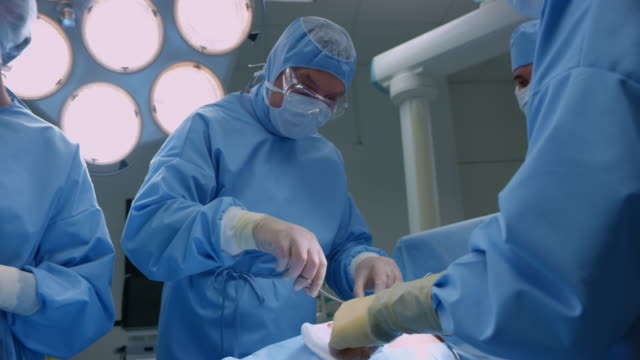 Male surgeon removing tissue during an operation