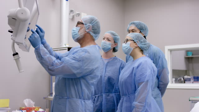 male surgeon reviews patient's medical condition with surgical team before operation - operation stock videos & royalty-free footage