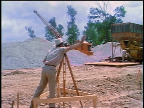 vídeos y material grabado en eventos de stock de 1957 rear view male surveyor looking through level + signaling with hands / crane in background - 1957