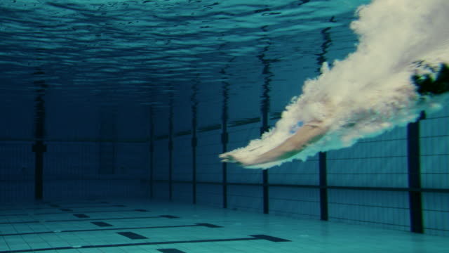 Male Swimmer Jumping Into Pool